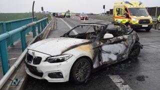 Řidič dodávky přehlédl BMW stojící u krajnice dálnice. Po nehodě shořelo, jeho šofér bojuje o život